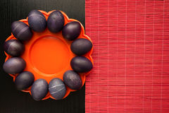 Twelve purple easter eggs on an orange plate, on a black wooden Royalty Free Stock Photos