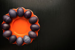 Twelve purple easter eggs on an orange plate, on a black wooden Royalty Free Stock Photography