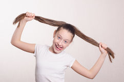 Twelve year old girl holding hair and tongue out Royalty Free Stock Photos