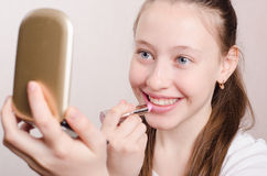 Twelve year old girl paints lips with lipstick Royalty Free Stock Images