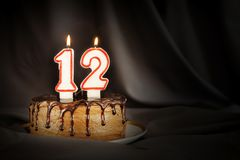 Twelve years anniversary. Birthday chocolate cake with white burning candles in the form of number Twelve. Dark background with black cloth stock image