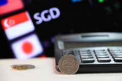 Twenty cents Singapore coin on obverse SGD with black calculator and digital board of currency exchange money. stock photography