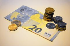 A twenty euro note and some coins. A twenty-euro bill and on it some euro coins: 1 cent, 5 cent, 10 cent, 20 cent, 1 euro Stock Images