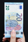 Twenty Euro on hand. And gold coins for background Stock Photo