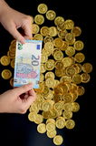 Twenty Euro on hand and gold coins Royalty Free Stock Photography