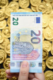 Twenty Euro on hand and gold coins Royalty Free Stock Image