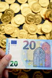 Twenty Euro on hand and gold coins Royalty Free Stock Photo