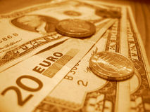 Twenty euros and ten dollars. Euros and dollar in sepia color with coins royalty free stock photography