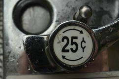 Twenty five cent coin slot and lever. Close-up detail of the coin slot  for quarter with price and lever to activate the coin-operated binoculars in park Royalty Free Stock Image