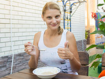 Twenty-five girl eating cereal breakfast on the veranda and shows class. Twenty-five girl eating delicious cereal breakfast on the veranda and shows class Royalty Free Stock Photo