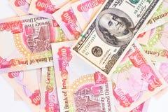 Twenty five thousand notes. Background of twenty five thousand iraqi dinar notes with a hundred dollar bill Stock Photo