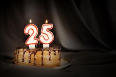 Twenty five years anniversary. Birthday chocolate cake with white burning candles in the form of number Twenty five. Dark background with black cloth royalty free stock photo