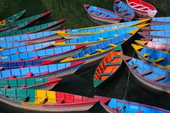 Twenty-four Rowboats on a Lake in Nepal. Twenty-four brightly colored hand-painted rowboats on a  fresh water lake in Nepal Royalty Free Stock Photos