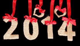 Twenty-fourteen of the tissue, hearts and red bows. Caption twenty fourteen decorated with red bows and ribbons isolated on black Stock Photos