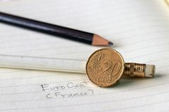 Twenty France euro cent on reverse, a map, next to the facial value, symbolizes the gathering of the nations of the European Union. With two pencil on the book stock image