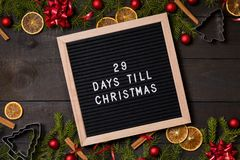 29 Days till Christmas countdown letter board on dark rustic wood. Twenty nine Days till Christmas countdown felt letter board flatlay on dark rustic wood table royalty free stock photography