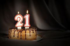 Twenty one years anniversary. Birthday chocolate cake with white burning candles in the form of number Twenty one. Dark background with black cloth royalty free stock photography