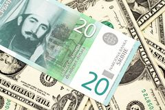 A twenty Serbian dinar with American one dollar bills. A close up of a green and white, twenty Serbian dinar bank note on a background of American one dollar royalty free stock photo