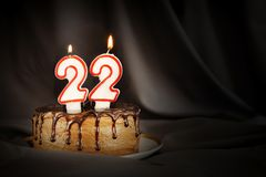 Twenty two years anniversary. Birthday chocolate cake with white burning candles in the form of number Twenty two. Dark background with black cloth royalty free stock photos