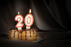 Twenty years anniversary. Birthday chocolate cake with white burning candles in the form of number Twenty. Dark background with black cloth royalty free stock photography