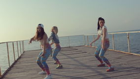 Twerk by young energetic teen girls on a wooden pier near the sea stock footage