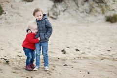 Twi little sisters at the beach on autumn Royalty Free Stock Images