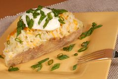 Twice baked potato with scallions, cheese and sour cream. A twice baked potato with scallions, cheese and sour cream Stock Photography