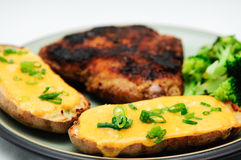 Twice baked potato smothered with cheese and green onions Stock Photo