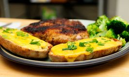 Twice baked potato smothered with cheese and green onions with a. Breaded pork chop and vegetables Stock Photography