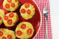 Twice baked potatoes with cheese and tomatoes on a red plate Royalty Free Stock Image