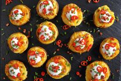 Twice baked potatoes halves, top view. Twice baked potatoes halves loaded with grated cheddar cheese, bacon, chili peppers slices, sour cream and sprinkled with Royalty Free Stock Image