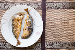 Twice of fried fish on white dish with Thai art style on backgro. Twice of fried fish on white dish with Thai art style background Stock Photography
