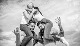 Twice fun on double date. Friendship of families. Couples in love having fun. Men carry girlfriends on shoulders. Summer stock photography