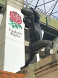 Twickenham gate statue. Bronze statue of rugby player at the gates of Twickenham, the home of Englan Rugby, with the organisation's logo in the background Royalty Free Stock Photography