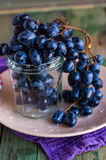 Twig of blue grapes in a glass on a plate, raw food Royalty Free Stock Photo