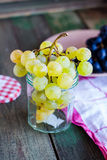 Twig of green grapes in a glass, vegan raw food Royalty Free Stock Image