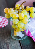 Twig of green grapes in a glass, vertically, wine Stock Photos