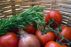 Twig with tomatoes, onions, and rosemary in a wicker basket. Stock Photo