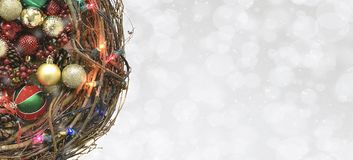 A twig wreath filled with holiday ornaments and lights. Christmas Decorations: A twig wreath filled with holiday ornaments and lights on a silver bokeh royalty free stock image