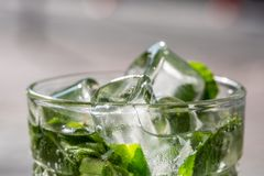 Twigs green mint in mojito with slices lime, ice cubes, straw, macro, texture. Blur royalty free stock photography