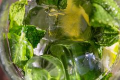 Twigs green mint in mojito with slices lime, ice cubes, straw, macro, texture. Blur stock images