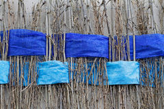 Twigs with interwoven wide blue ribbons of felt Stock Photo
