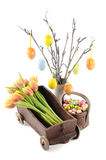 Twigs, tulips and Easter candy in a basket Royalty Free Stock Photos
