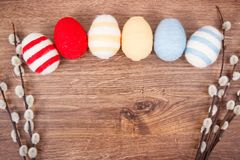 Twigs of willow and colorful Easter eggs wrapped woolen string on rustic board, copy space for text Stock Photography