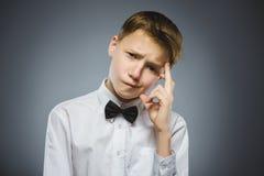 Twijfel, uitdrukking en mensenconcept - jongen die over grijze achtergrond denken royalty-vrije stock afbeeldingen