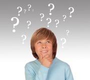Twijfelachtig preteen jongen met vele vraagsymbolen Stock Fotografie