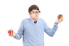 Twijfelachtige kerel die een appel en een doughnut houdt Stock Afbeeldingen