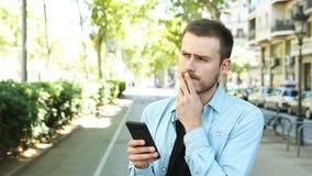 Twijfelachtige mens die smartphone in de straat met behulp van