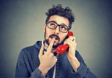 Twijfelachtige mens die telefoongesprek hebben stock afbeeldingen