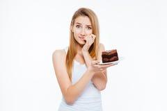 Twijfelachtige vrouw op dieet die en stuk van cake denken houden stock foto's